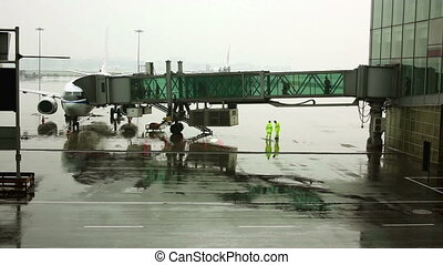 passengers walking on boarding bridge at airport jetway