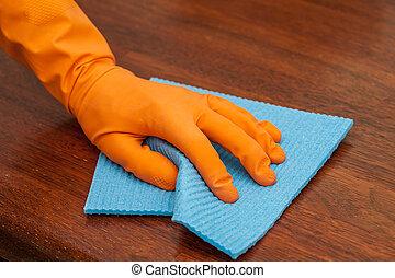 Table polishing - A man with a glove polishing a woodentable...