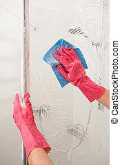 Shower polishing - A man polishing a shower with a wet rag