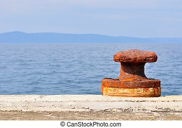 Old, rusty mooring bollard on port of Podgora, Croatia Space...