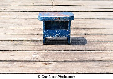 Old small wooden blue fishing chair alone on wooden fishing...