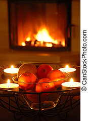 Fruits and candles nearby fireplace
