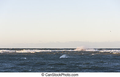 Stormy sea with white wave hiting a rock in background