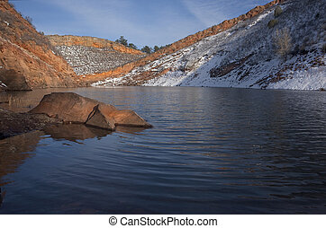 mountain lake with sandstone cliffs and snow