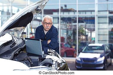 Mature auto mechanic. - Mature auto mechanic working in car...