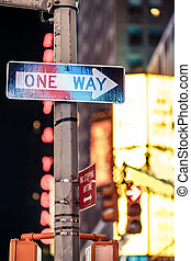 One way New York traffic sign with illuminated and blurred...