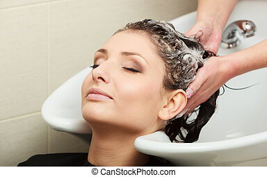 Hairstylist washing woman hair. Hairdressing beauty salon -...
