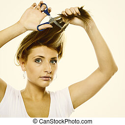 Unhappy woman cutting her hair with scissors - Damaged dry...