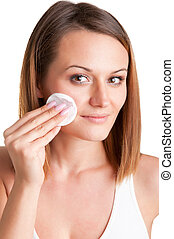 Woman Removing Make-Up - Woman removing make-up with a...