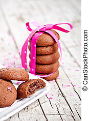 plate of fresh chocolate cookies with pink ribbon and confetti