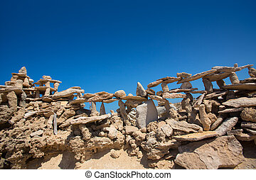 Stone figures on beach shore of Illetes beach in Formentera...