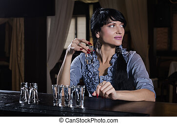 Stylish young woman drinking alone at the bar with a row of...