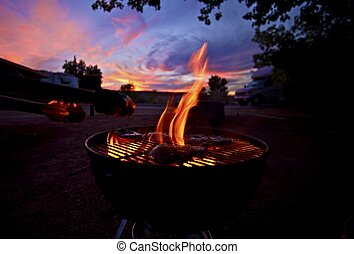 Barbecue at Sunset. Tasty Steaks on BBQ fire. Camping and...