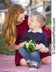Young Boy Holding Christmas Gift with His Mom in Park