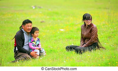 Mongolian family sitting on grass