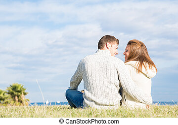 Lovers back in the grass next to the beach