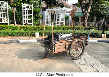 Cleaning equipment on trolley in village.