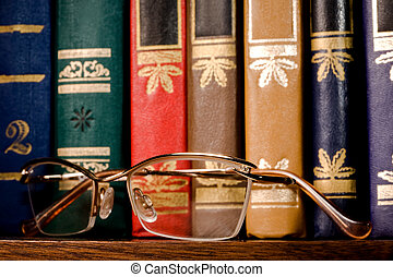 Glasses in a gold frame on a book shelf