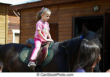 Horseback riding child in yard