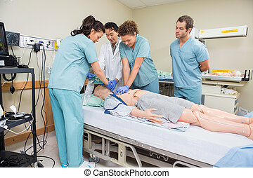 Nurse Performing CPR On Dummy Patient - Female nurse...