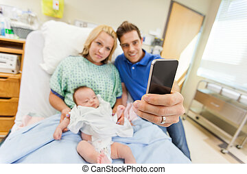 Man with woman and newborn babygirl taking selfportrait...