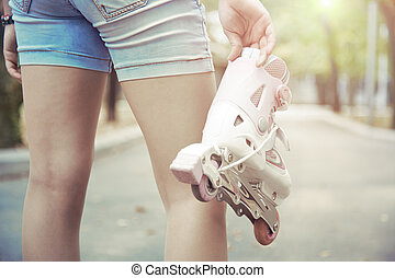 Roller skating - Teenager holding roller skates in park....