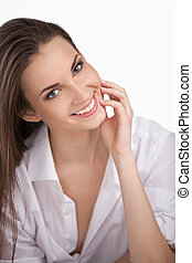 Wearing her boyfriend shirt. Beautiful young woman in white shirt holding hand on chin and smiling while isolated on white