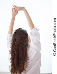 Good morning! Rear view of young woman in shirt stretching...