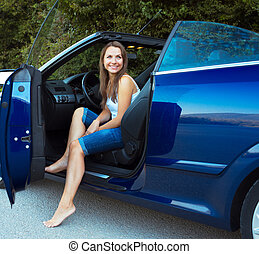 Smiling caucasian woman in a cabriolet car
