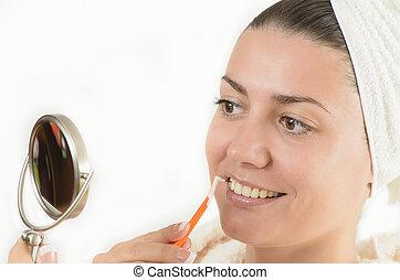 Interdental Brush - Young woman using an interdental brush
