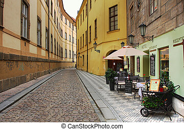Old street with small hotel and outdoor restaurant in...