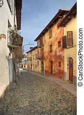 Narrow paved street among houses in Saluzzo, Italy.