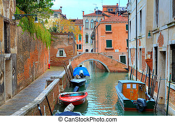 Boats on canal among houses. Venice, Italy.