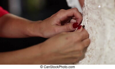 Lacing wedding dress - Bridesmaid helps to lace wedding...