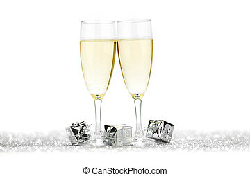 Two champagne flutes and gifts on shiny background