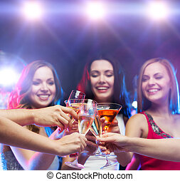 three smiling women with cocktails and disco ball - party,...