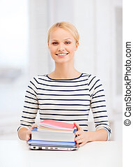 smiling student with laptop, books and notebooks - education...