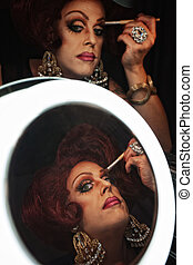 Woman Applying Eye Shadow - Drag queen applying makeup in...