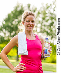 blond woman with a water bottle and towel