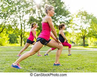Jogging coach streching with clients - Portrait of three...