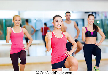group of smiling people exercising in the gym - fitness,...