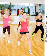 group of concentrated people exercising in the gym -...