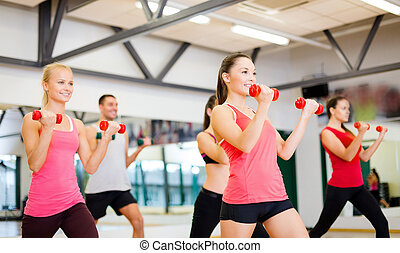 group of smiling people working out with dumbbells -...