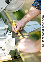 Carpenter Marking On Wood Using Ruler At Table Saw - Closeup...