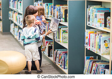 Teacher With Children Selecting Book In Library - Young...
