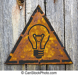 Light Bulb Icon on Rusty Warning Sign. - Light Bulb Icon on...