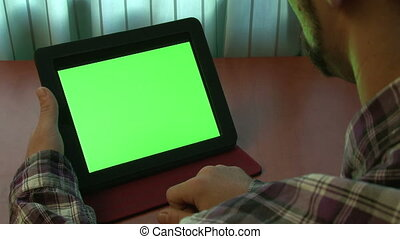 Man using digital tablet with a green screen to add your own...
