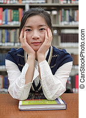 Student sitting at a desk near library