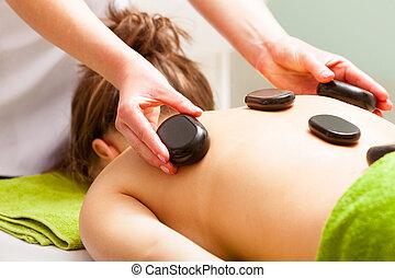 Spa salon. Woman relaxing having hot stone massage....