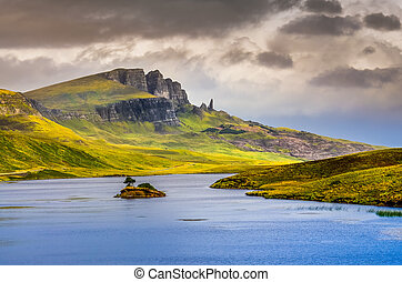 Landscape view of Old Man of Storr rock formation and lake,...